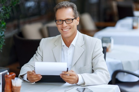 blissful: Much work to do. Cheerful blissful adult man sitting at the table and holding folder while expressing gladness