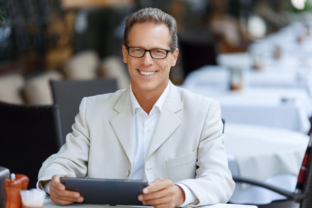 expressing joy: Life fully. Pleasant cheerful adult man sitting at the table and holding laptop while expressing joy Stock Photo