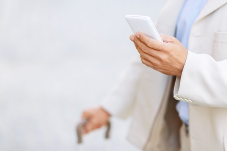 portmanteau: Lets make a call. Close up of mobile phone in hands of adult man holding it and going to make a call Stock Photo