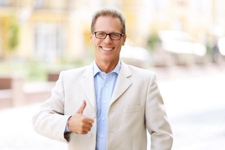 blissful: Everything is great. Overjoyed blissful handsome adult man thumbing up and smiling while standing in the street Stock Photo