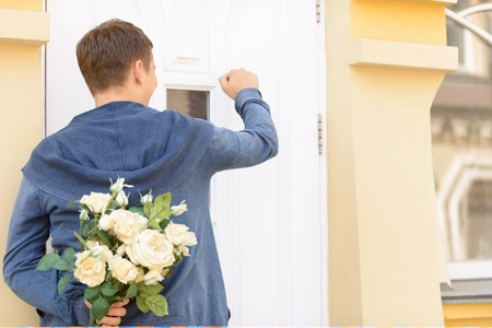 guy standing: Ready for surprise. Nice cheerful upbeat young guy holding bouquet of flowers and standing near the door while knocking Stock Photo