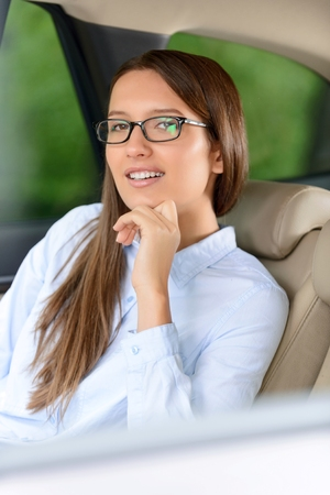 glance: Confidence in glance. Pleasant self assertive young beautiful holding hand under the chin while sitting in the car
