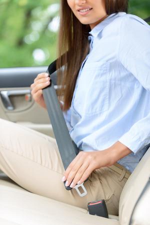 cinturon seguridad: Salva tu vida. Close up de joven sonriente sentado en el coche y usar el cinturón de seguridad Foto de archivo