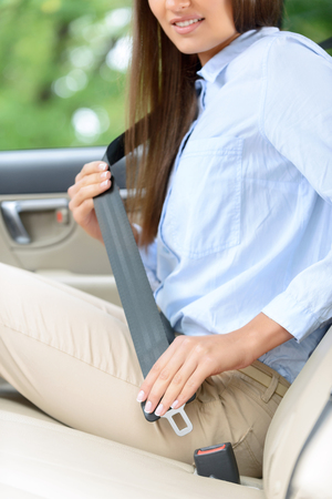safety belt: Save your life. Close up of young smiling woman sitting in the car and using safety belt Stock Photo