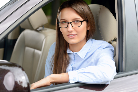 agreeable: Modern woman. Agreeable attractive delighted lady sitting at the wheel and driving a car while feeling glad