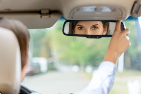 to be pleasant: Be confident. Pleasant attractive delighted young woman holding the glass in the car and looking at you while sitting at the wheel Stock Photo