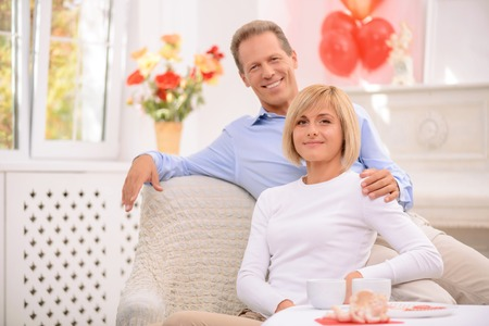 agreeable: Real love. Nice agreeable smiling couple sitting in the armchair and  bonding to each other while expressing gladness Stock Photo