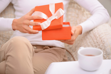 agreeable: Best surprise. Close up of adult agreeable man opening present and sitting in the armchair while drinking tea