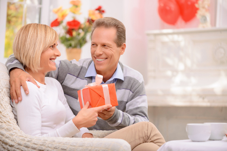 st valentine: It is for you. Overjoyed happy adult couple holding present and sitting on the settee while celebrating St Valentine Day
