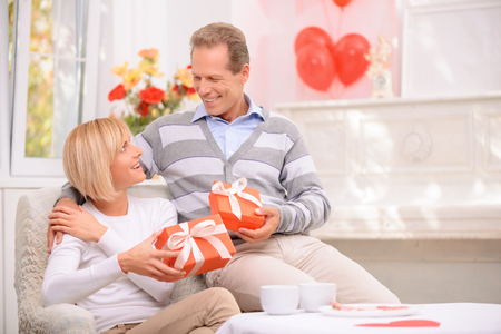 st  valentine: Nice celebration. Pleasant vivacious smiling adult couple holding presents and sitting in the armchair while celebrating St Valentine day Stock Photo