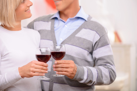 agreeable: Romantic atmosphere. Agreeable loving adult happy couple holding glasses and drinking wine while bonding to each other