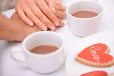 sublime: Sublime love. Close up of hands of nice loving couple holding them together on the table while drinking tea