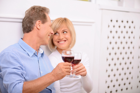 affinity: Pleasant affinity. Cheerful delighted adult couple holding glasses and drinking wine while bonding to each other