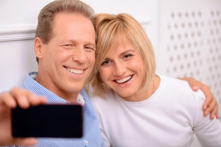 say cheese: Say cheese. Overjoyed smiling adult couple smiling and making photos while bonding to each other