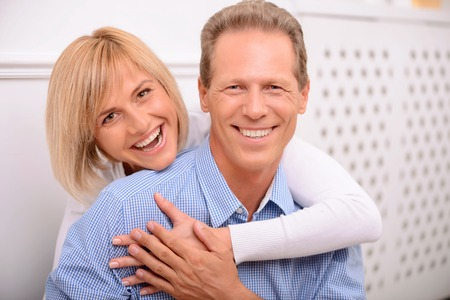 expressing joy: Amour in air. Vivacious pleasant smiling adult couple embracing and expressing joy while having great time together Stock Photo