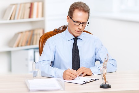 to be pleasant: Be a real professional. Pleasant professional lawyer holding pan and writing while sitting at the table