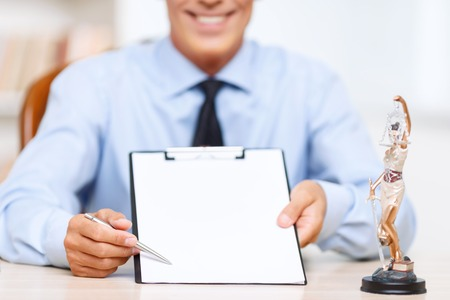 agreeable: Put your signature.  Professional agreeable lawyer holding folder and pointing with the pen while sitting at the table Stock Photo