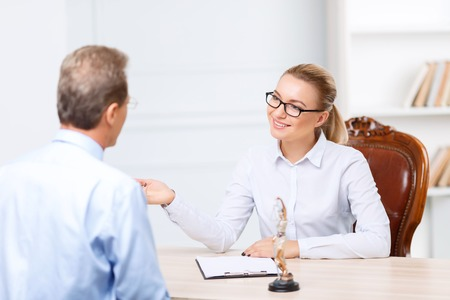 agreeable: Lets discuss it. Nice agreeable delighted lawyers sitting at the table and having conversation while being busy at  work