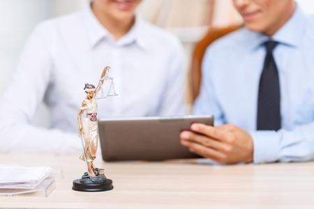 Gute Profis. Close up von kleinen Statue der Gerechtigkeit, der auf dem Tisch mit zwei professionellen Juristen auf dem Hintergrund arbeiten