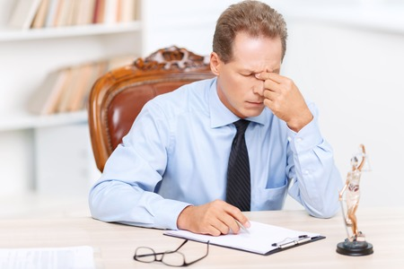 horribly: Horribly tired. Professional exhausted Lawyer holding his fingers on the nose and sitting at the table while feeling weary Stock Photo