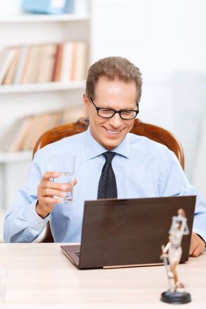 upbeat: Involved in work. Upbeat smiling handsome adult lawyer sitting at the table and drinking water while working on computer