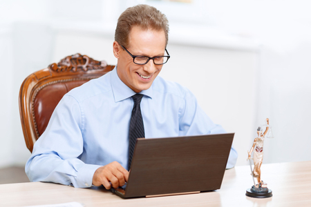 feeling positive: Busy at work. Vivacious pleasant delighted lawyer sitting at the table and working on the computer while feeling positive Stock Photo