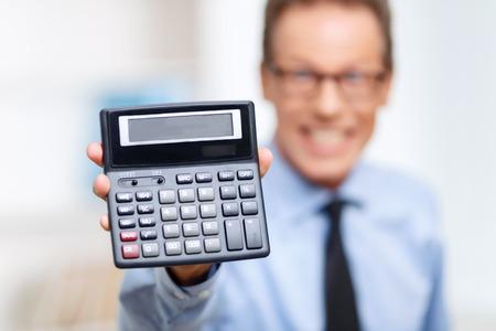 calculadora: Dispositivo de Wise. Enfoque selectivo de la calculadora en manos de abogado profesional sosteni�ndolo y participar en el trabajo
