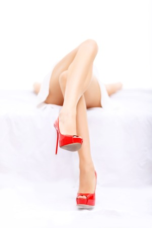 spiritual energy: ring girl. Close up of beautiful legs of attractive magnetic young woman lying o bed while seducing you