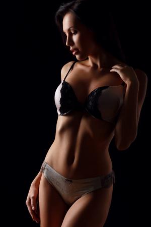 salud sexual: Mujer sensual. Atractiva chica magnética sexual mirando a un lado y te seduce, mientras que de pie aislado en fondo negro Foto de archivo