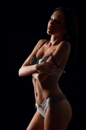 voluptuosa: Llena de placer. Voluptuosa chica atractiva magnética cruzando las manos y tentando mientras que de pie aislado en fondo negro