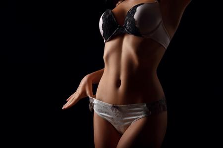 voluptuous: Sensaci�n de contenido. Cierre para arriba de muchacha sensual aturdidor voluptuosa seducir a usted mientras est� de pie en el fondo negro Foto de archivo