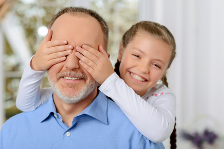 vivacious: Guess who. Pleasant vivacious little girl closing eyes of her grandfather while having fun together Stock Photo