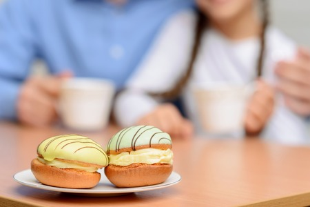 unforgettable: Unforgettable taste. Close up of nice biscuits lying on the plate with grandfather and little girl drinking tea in the background
