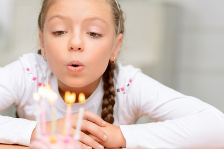 blue candles: Make a wish. Cheerful delighted little girl sitting at the table and blowing the candles while having birthday party Stock Photo