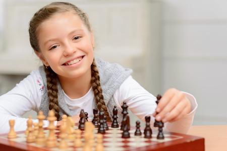Örömmel teli. Vidám, mosolygós kislány ül az asztalnál, és evincing öröm közben sakkozni