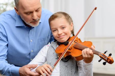 abuelo: Disfruta la música. Alegre niña sonriente la celebración de arco de violín, mientras que aprender a tocar el violín con su abuelo