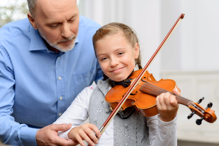 fiddle: Enjoy music. Cheerful smiling little girl holding fiddle bow while learning to play violin with her grandfather
