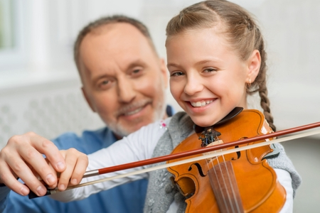Best player. Vivacious pretty delighted little girl holding fiddle bow and playing the violin with her grandfather