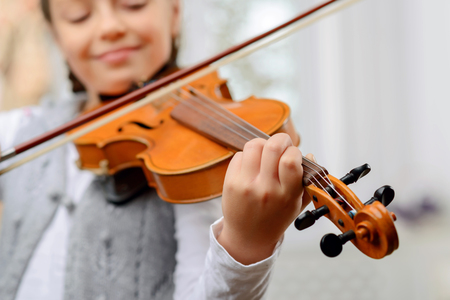 fiddle: A way to success. Close up of pleasant vivacious pretty girl holding fiddle bow and learning to play the violin Stock Photo