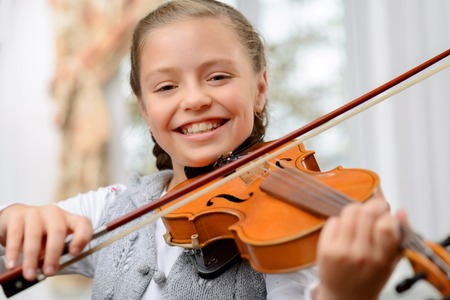 violins: Full of joy. Cheerful content little girl holding fiddle bow and violin while learning to play