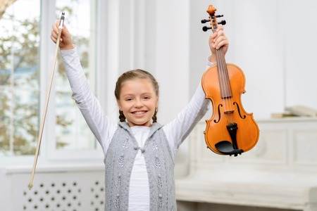 agreeable: I am the winner. Agreeable elated pretty little girl holding violin and keeping her hands up while evincing joy