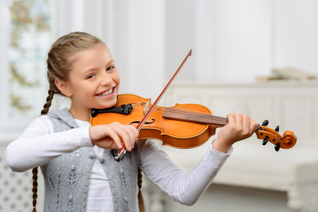 Like doing it. Cheerful blissful pretty little girl holding fiddle bowl and learning to play the violin while smiling