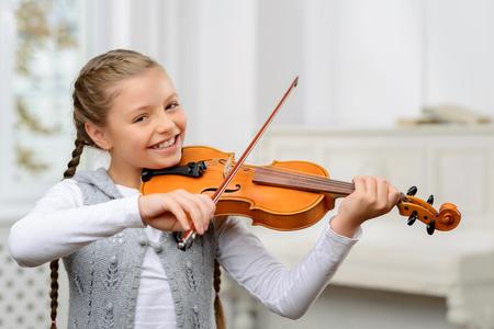 Mint csinálja. Vidám boldog szép kislány, aki hegedűn tál és a tanulás hegedülni miközben mosolyogva