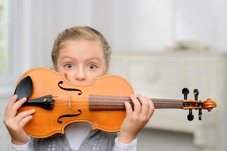 행복한 어린 시절. 그녀의 얼굴 앞에서 바이올린을 들고 음악 수업을하는 동안 뒤에 숨어있는 즐거운 긍정적 인 소녀