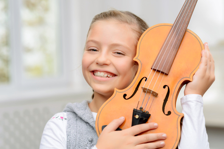agreeable: My favorite. Vivacious agreeable smiling little girl holding the violin near face and smiling while having music lesson