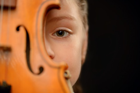 pathetic: Pathetic glance. Close up of the eue of little girl holding the violin and hiding behind it