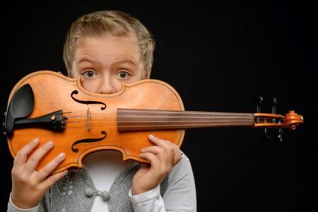 영감을 얻으십시오. 바이올린을 들고 검정색 배경에 서있는 동안 그녀의 입의 앞에 그것을 유지하는 긍정적 인 예쁜 소녀
