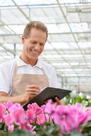 agreeable: Be precise. Agreeable content cheerful positive florist holding folder and making notes while being involved in work