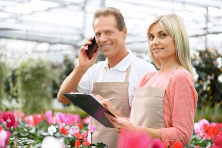 expressing joy: Work for you. Cheerful professional florists expressing joy and smiling while working in the greenhouse Stock Photo