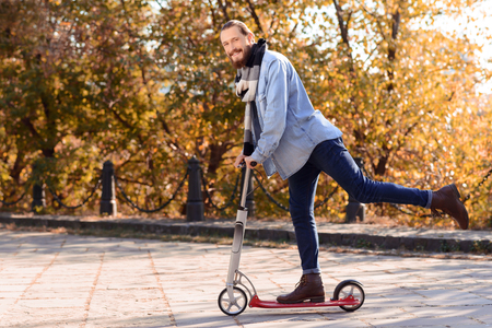 blissful: Pleasant handsome blissful bearded man holding the scooter and riding it while feeling delighted Stock Photo